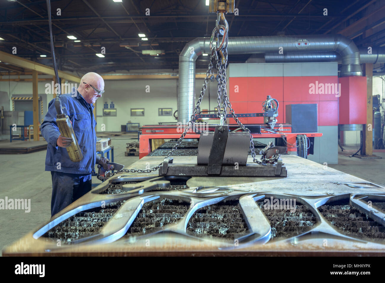 Worker with plasma cutter machine with steel offcuts in engineering factory - Stock Image