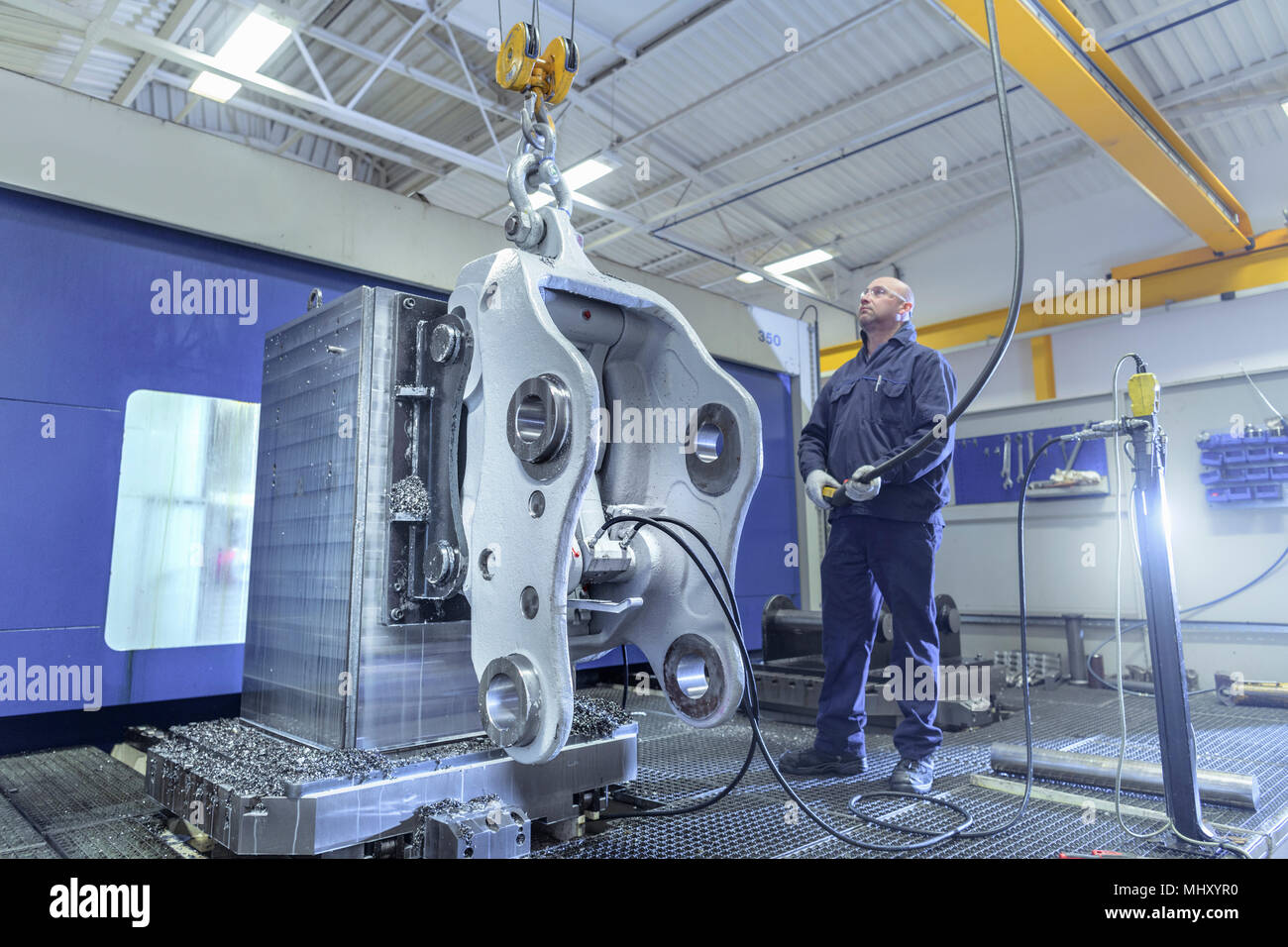 Engineer craning part into large CNC machine in engineering factory - Stock Image