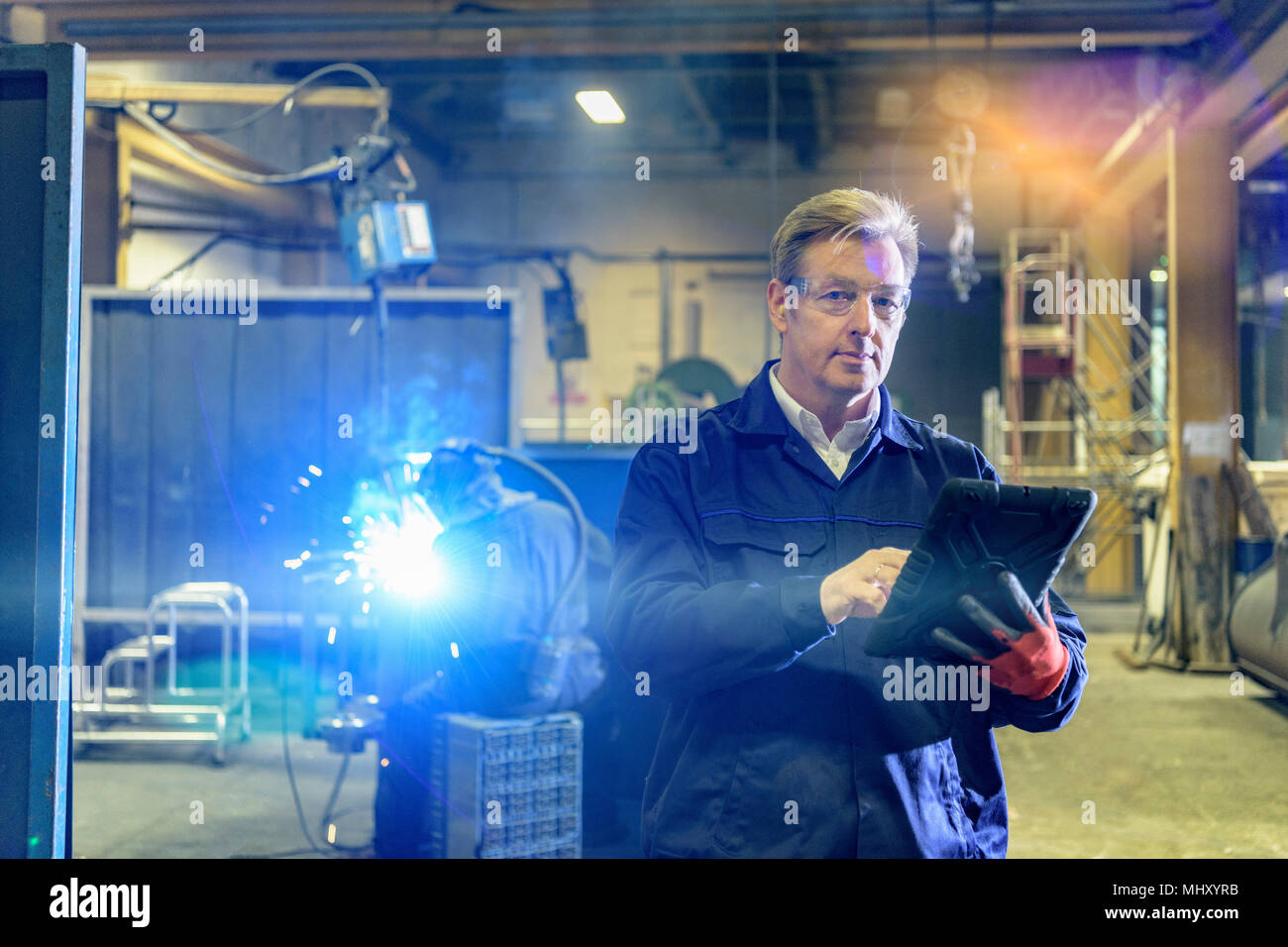 Manager with digital tablet in engineering factory - Stock Image