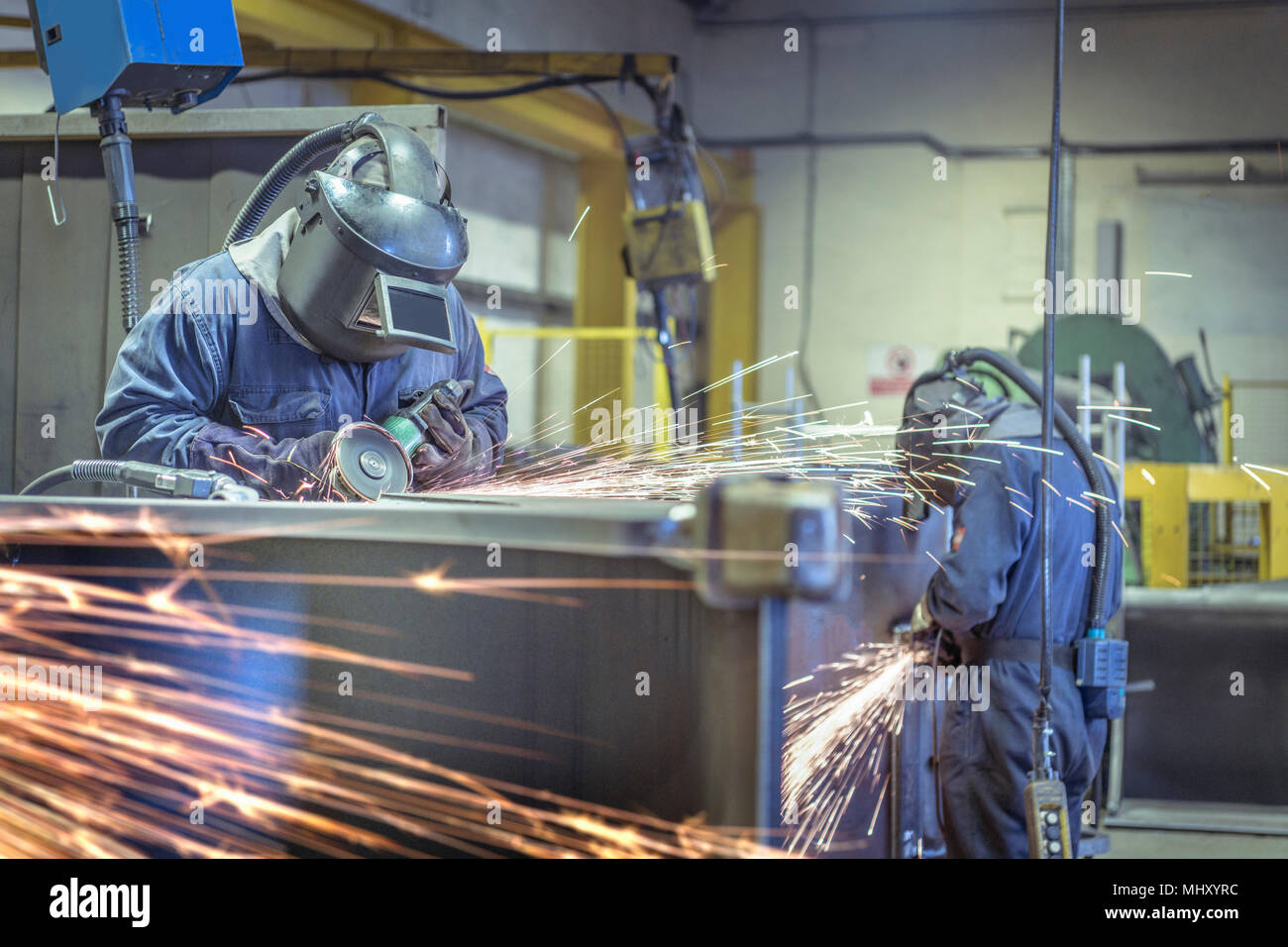 Workers using grinders in engineering factory - Stock Image