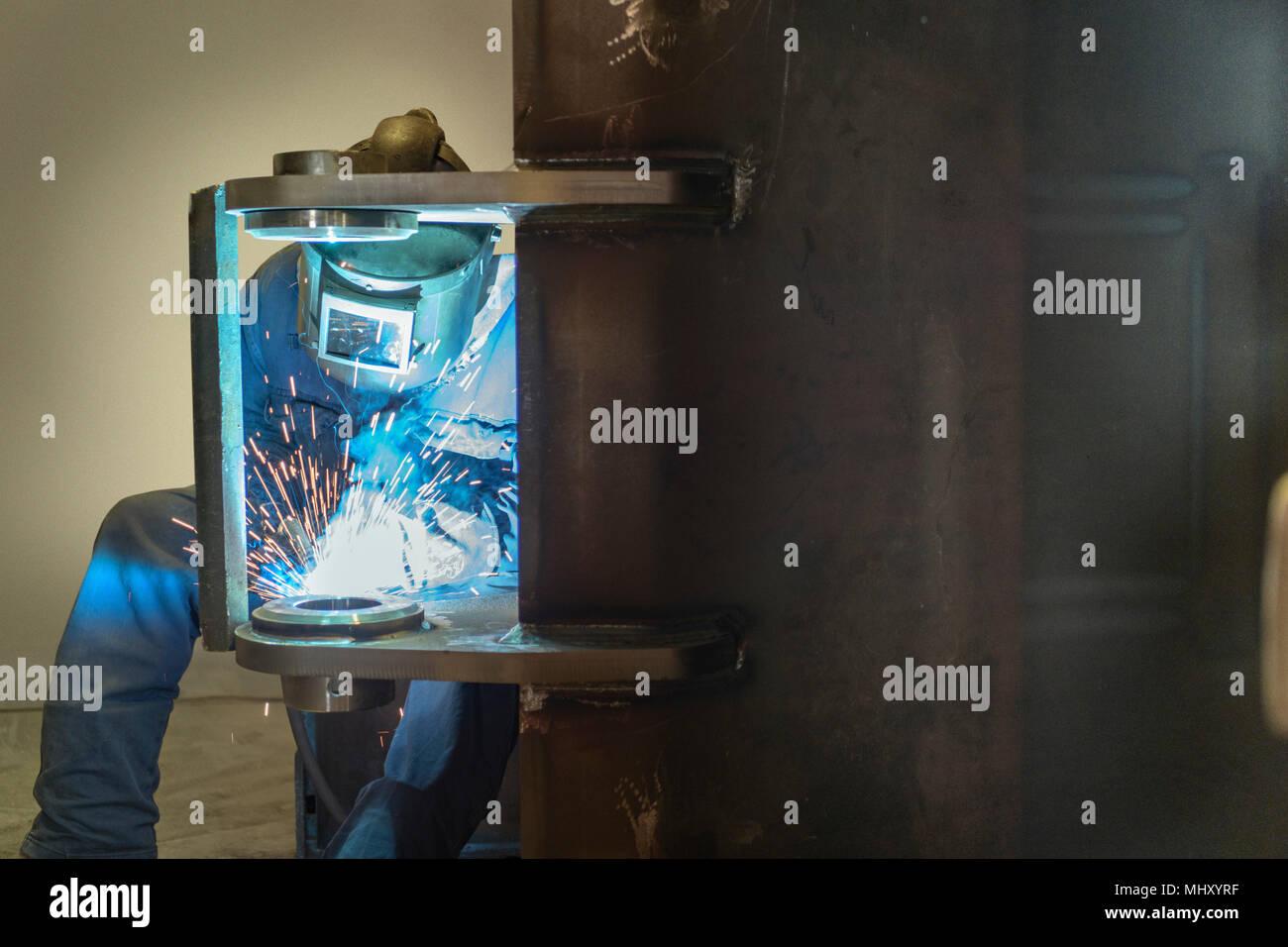 Welder welding part of digger bucket in engineering factory - Stock Image