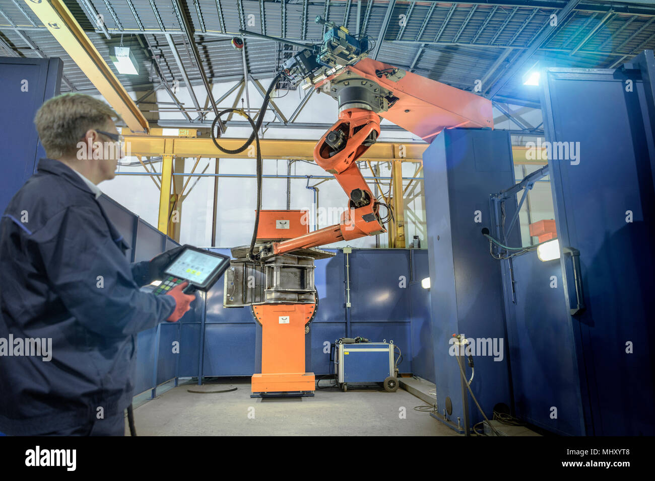 Engineer with controller in robotic welding bay in engineering factory - Stock Image