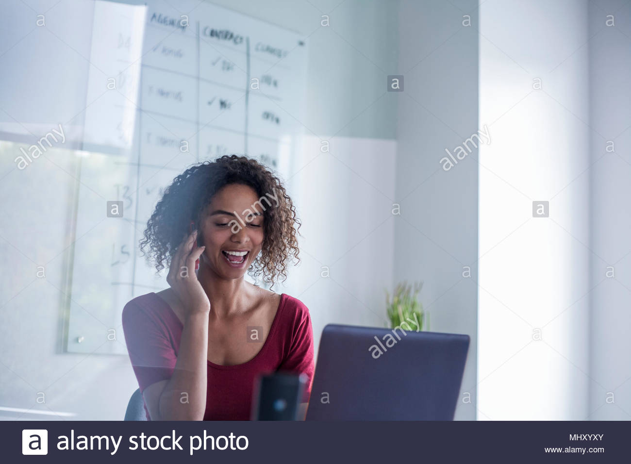 Businesswomen in office making telephone call smiling - Stock Image
