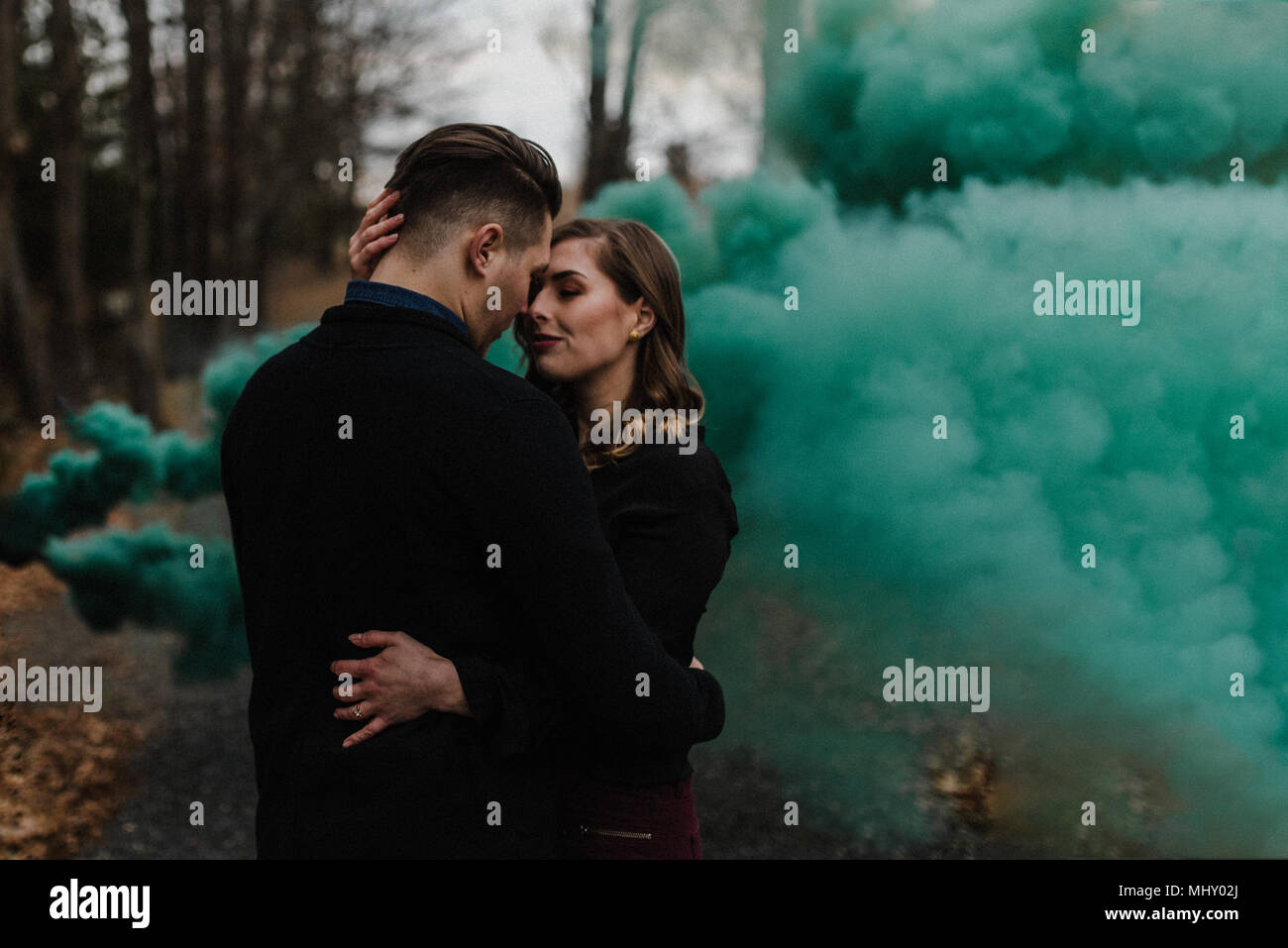 Young couple kissing in forest by green smoke cloud - Stock Image