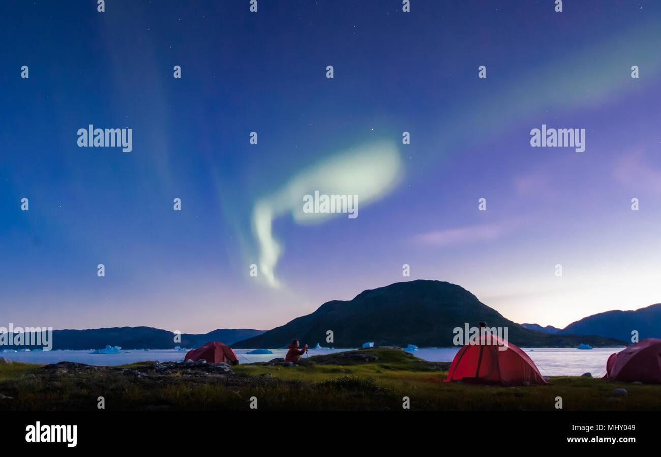 Landscape with tents by fjord and aurora borealis at night, Narsaq, Vestgronland, South Greenland - Stock Image