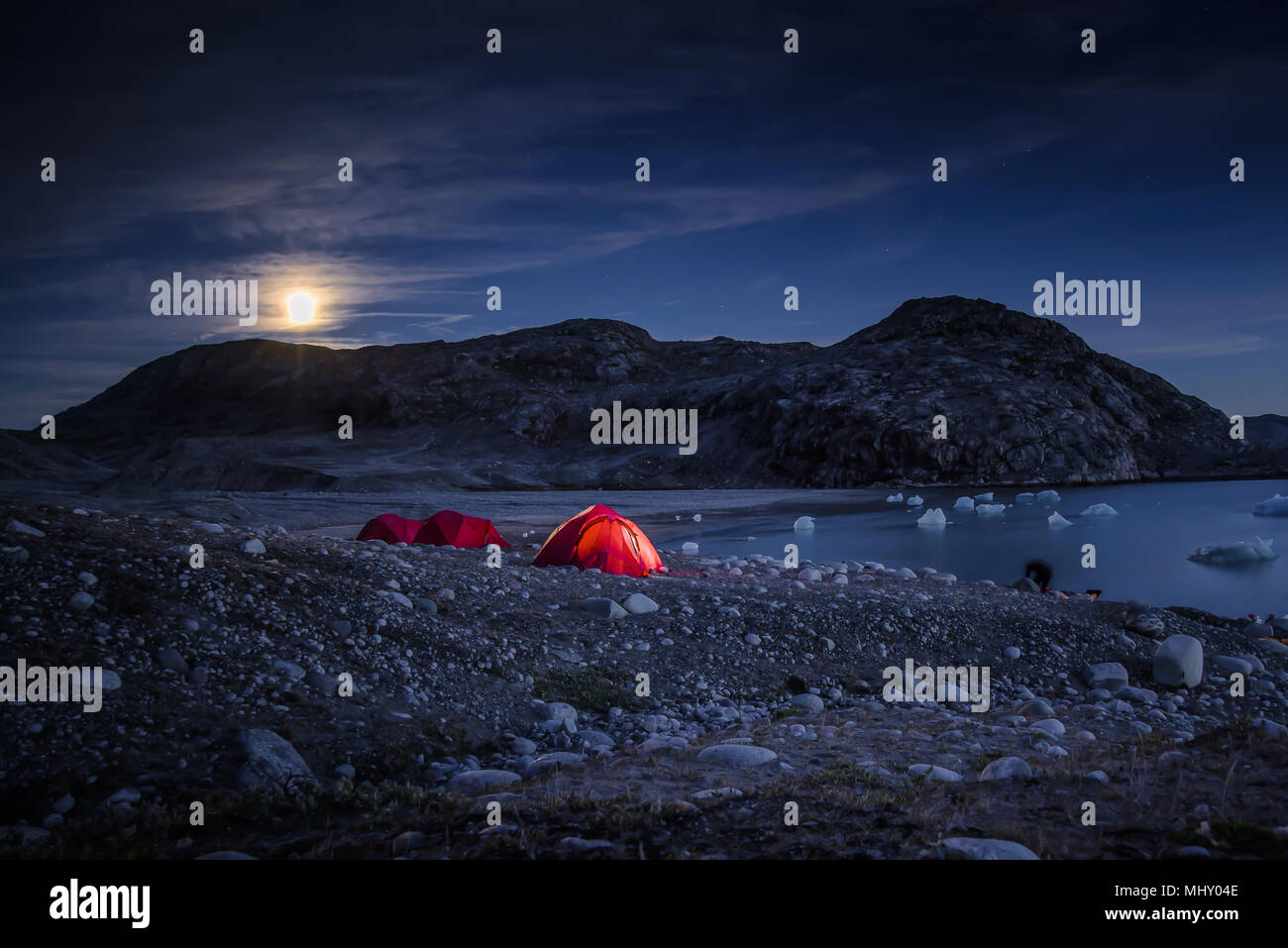 Landscape with tents by fjord and full moon at night, Narsaq, Vestgronland, South Greenland - Stock Image