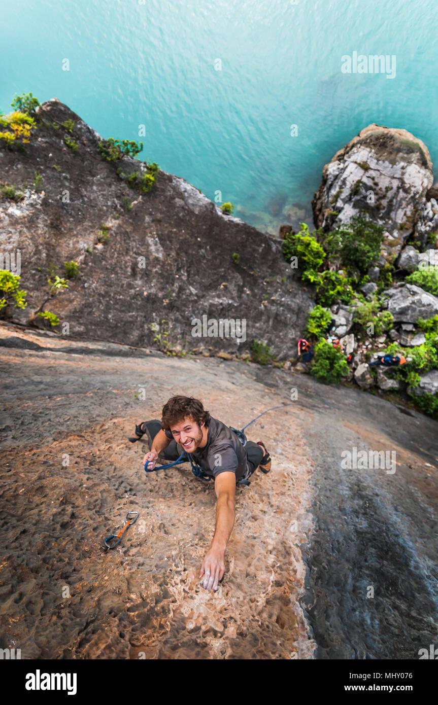 Man rock climbing on limestone rock, overhead view, Ha Long Bay, Vietnam - Stock Image