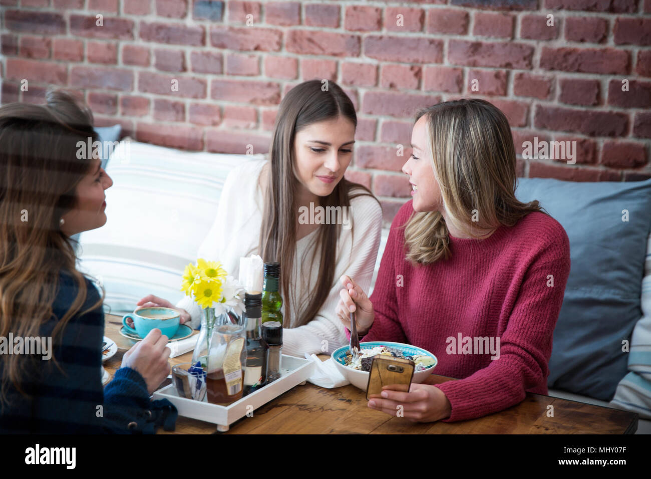 Three female friends, sitting together in cafe - Stock Image