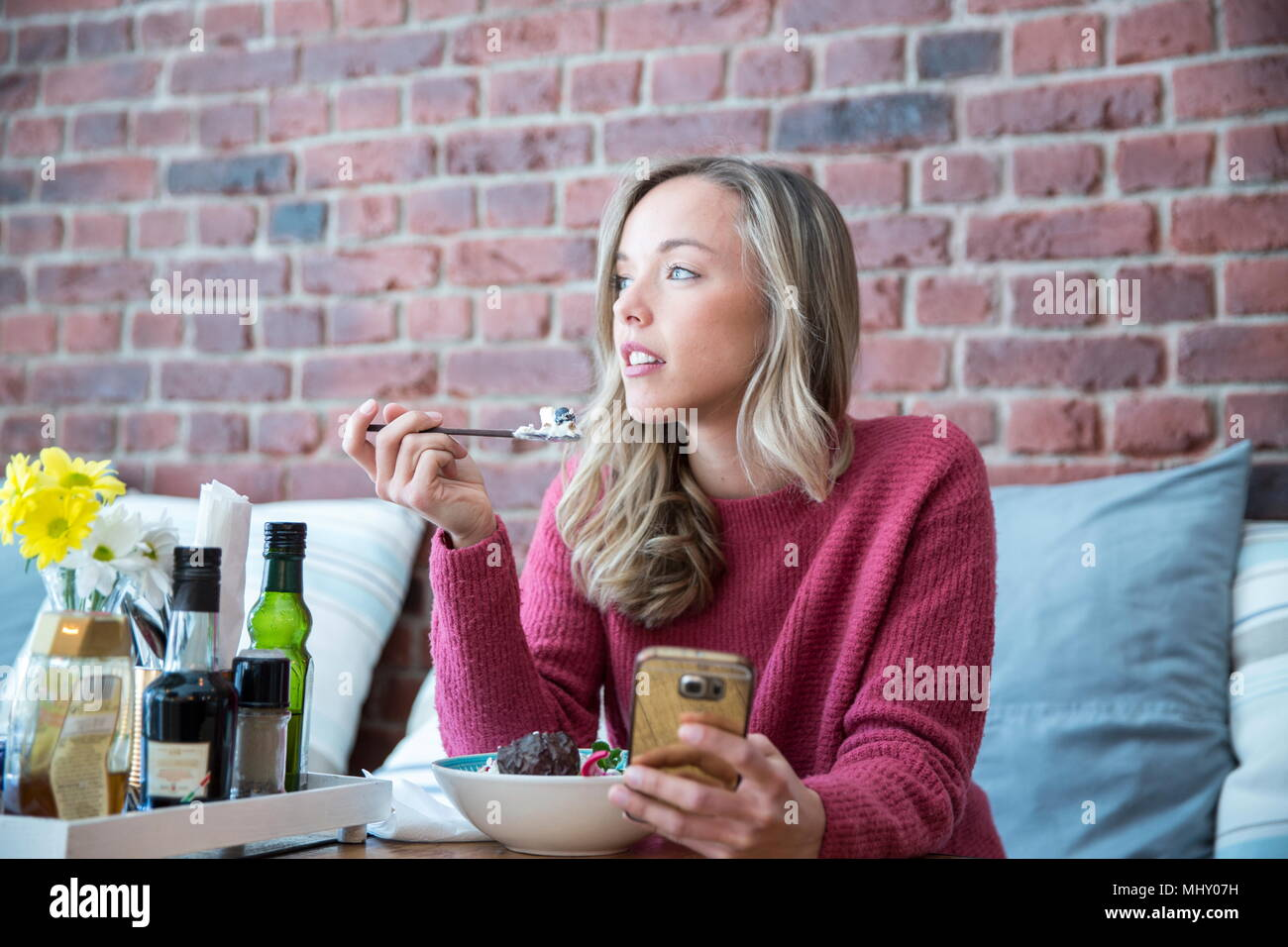 Woman sitting in cafe, eating bowl of muesli, holding smartphone - Stock Image