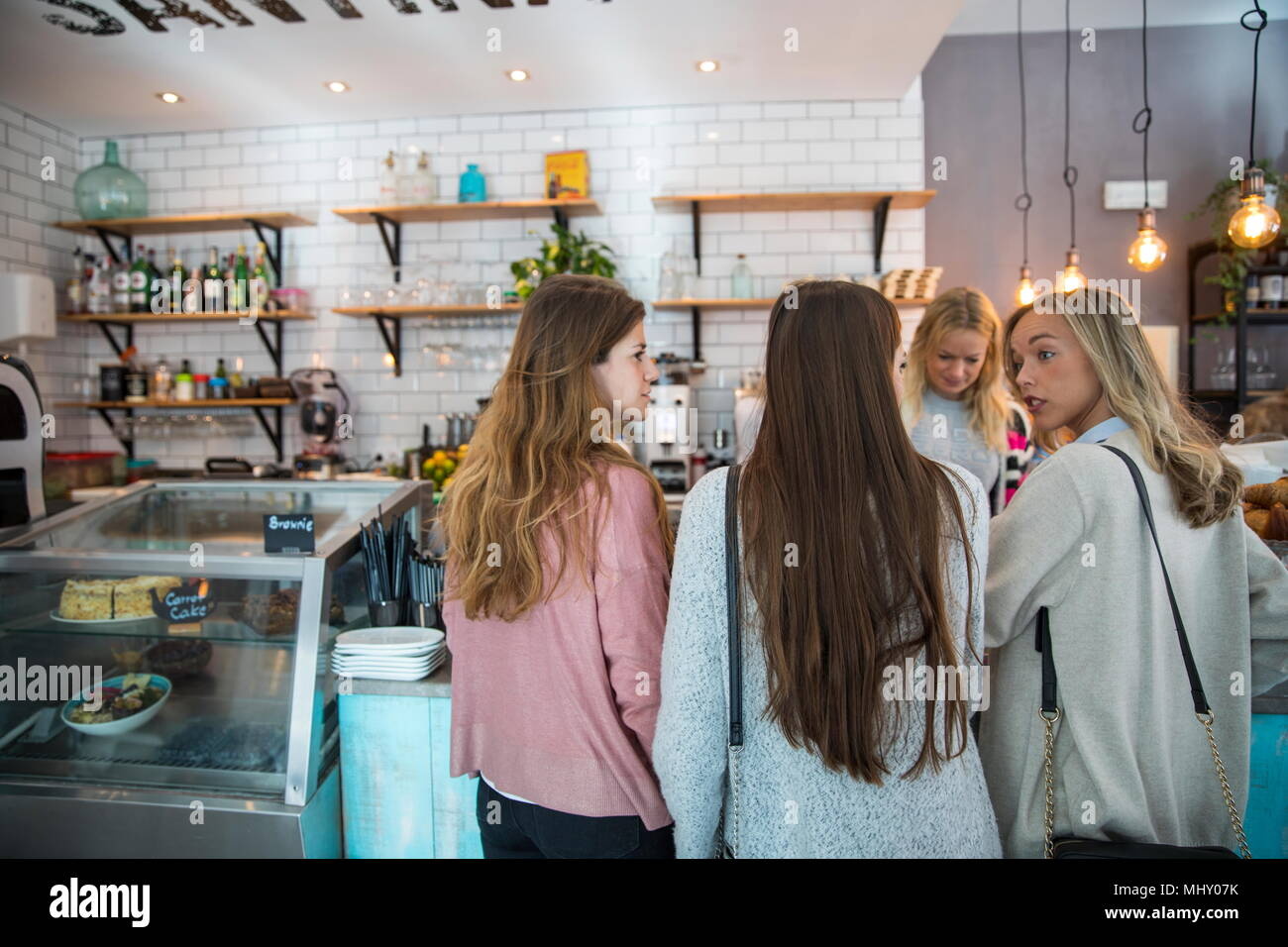Three female friends, standing at counter in cafe, rear view - Stock Image