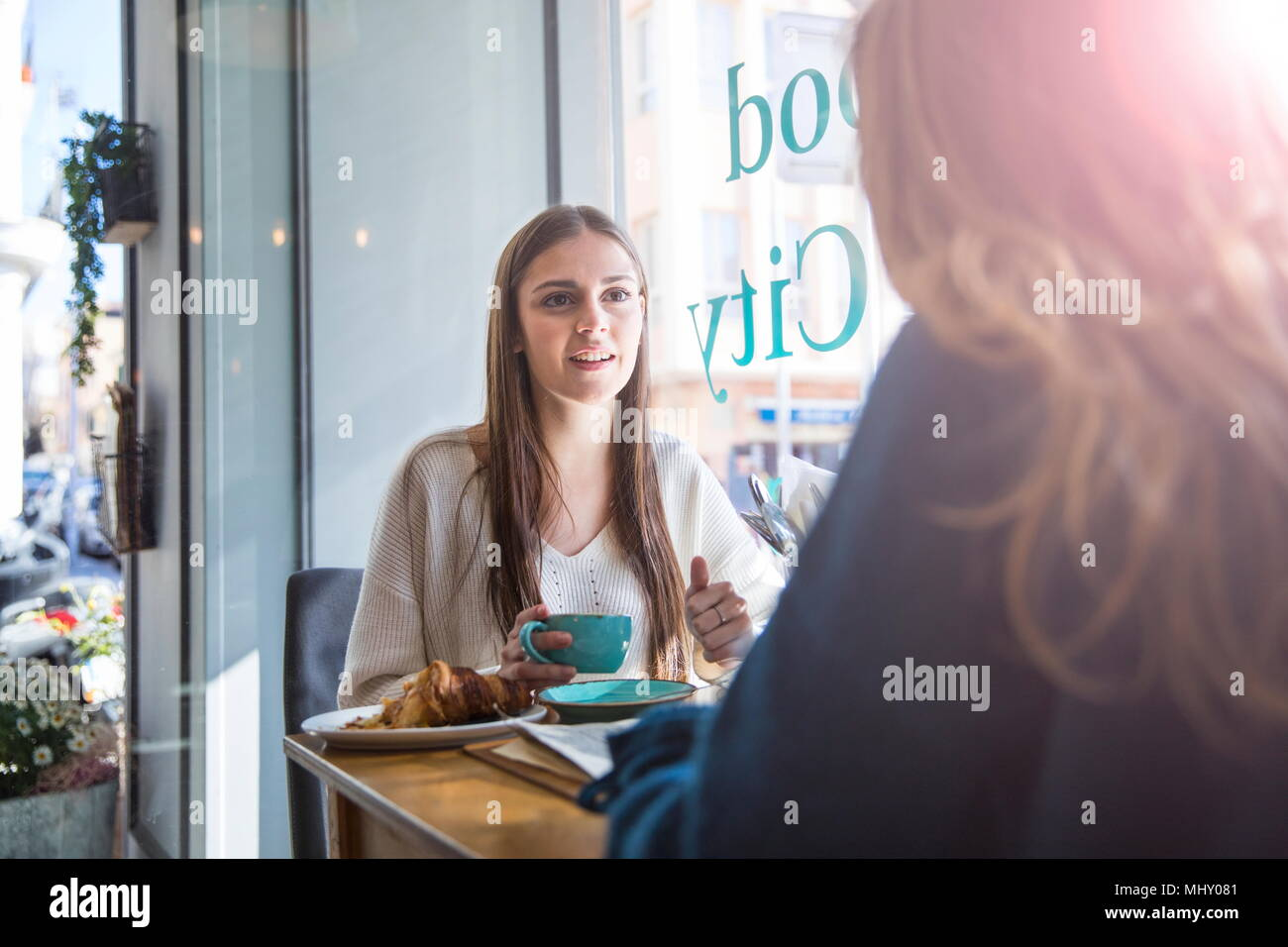 Two female friends sitting together in cafe, drinking coffee - Stock Image