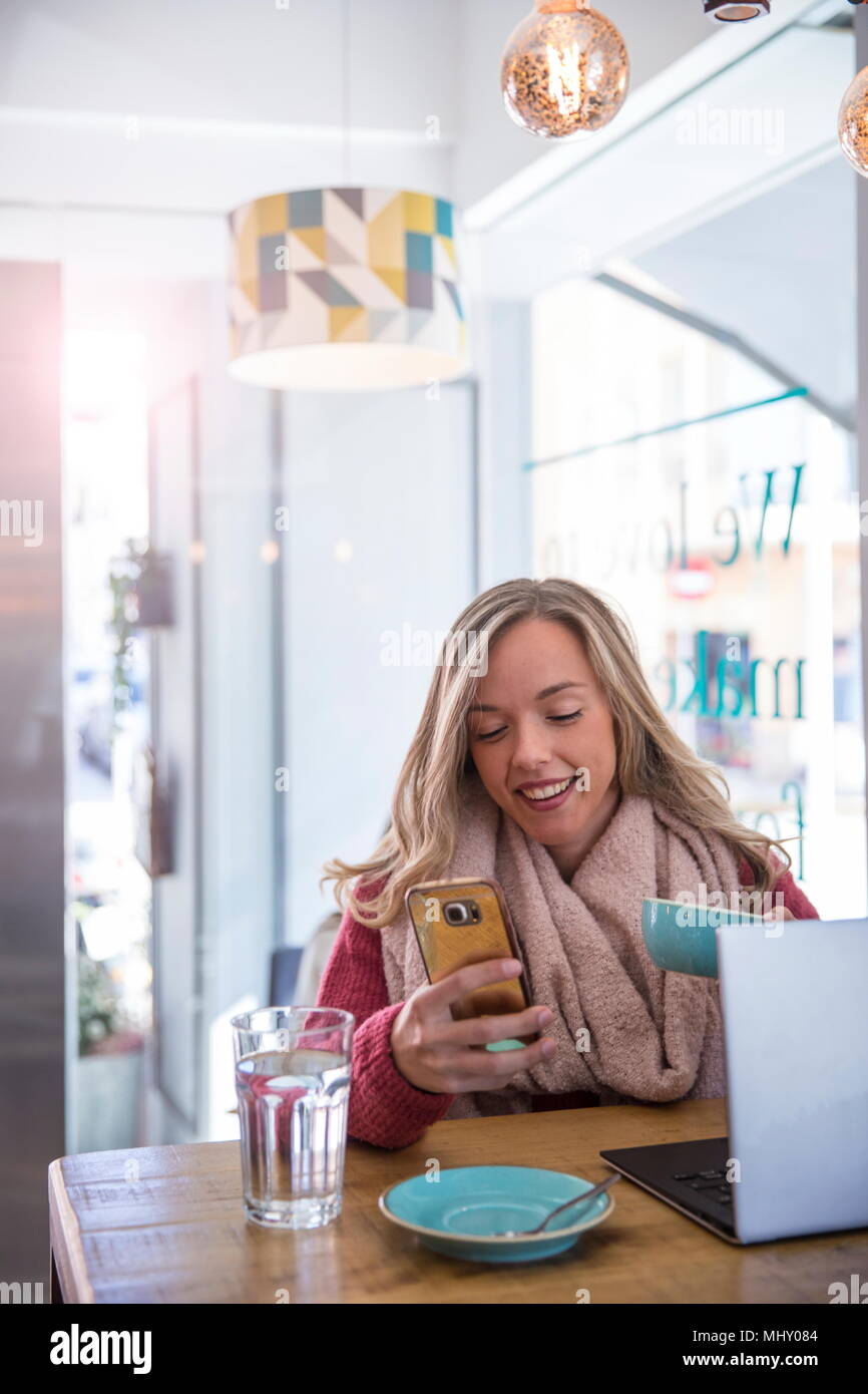 Woman sitting in cafe, looking at smartphone, holding coffee cup - Stock Image