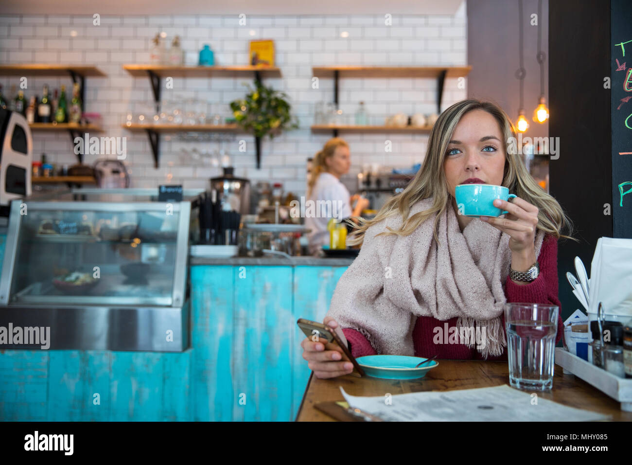 Woman sitting in cafe, holding smartphone, drinking coffee - Stock Image