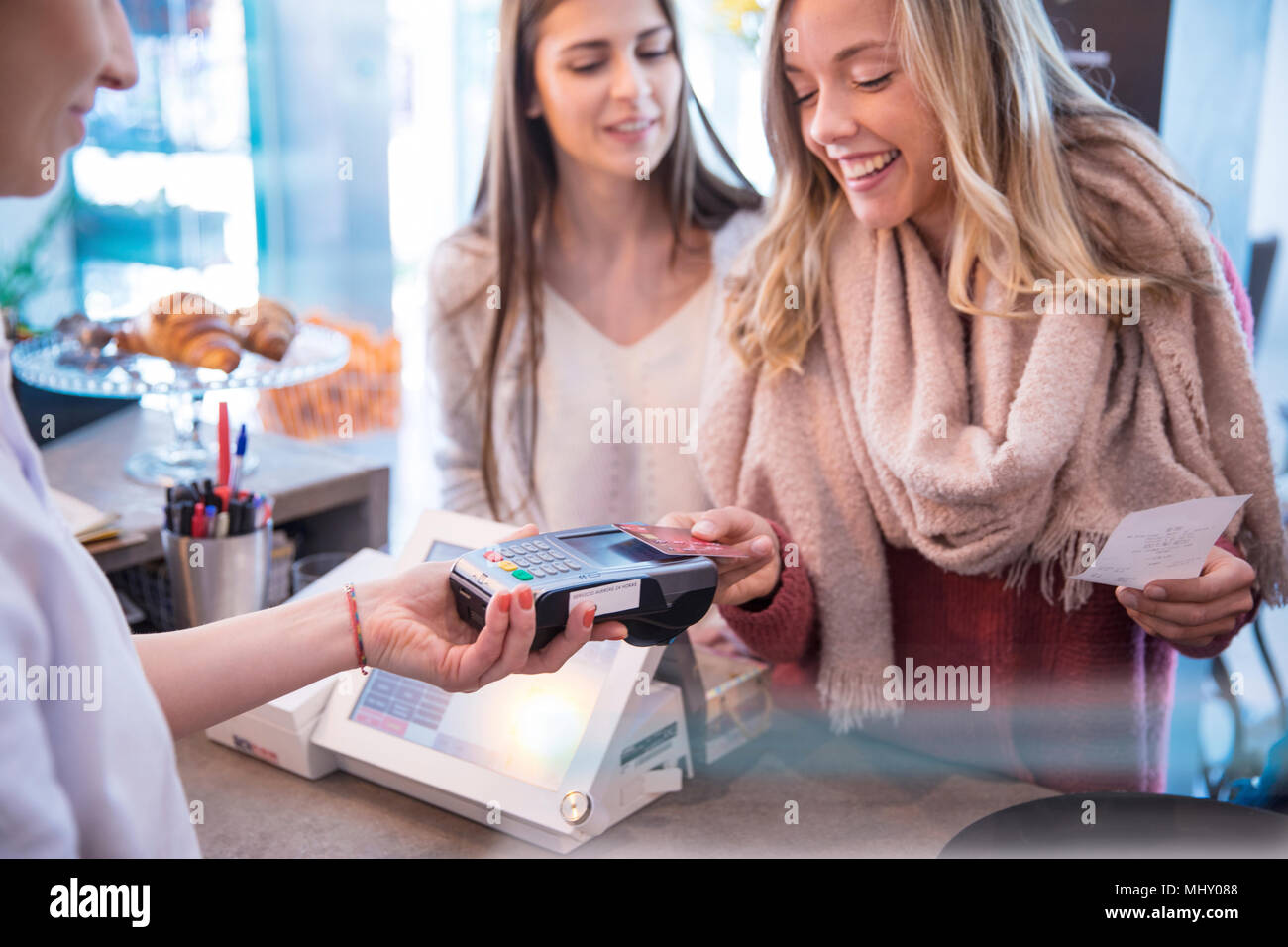 Female friends standing at counter in cafe, paying using credit card - Stock Image