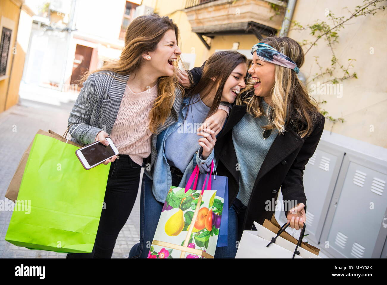Friends out shopping and laughing in street - Stock Image
