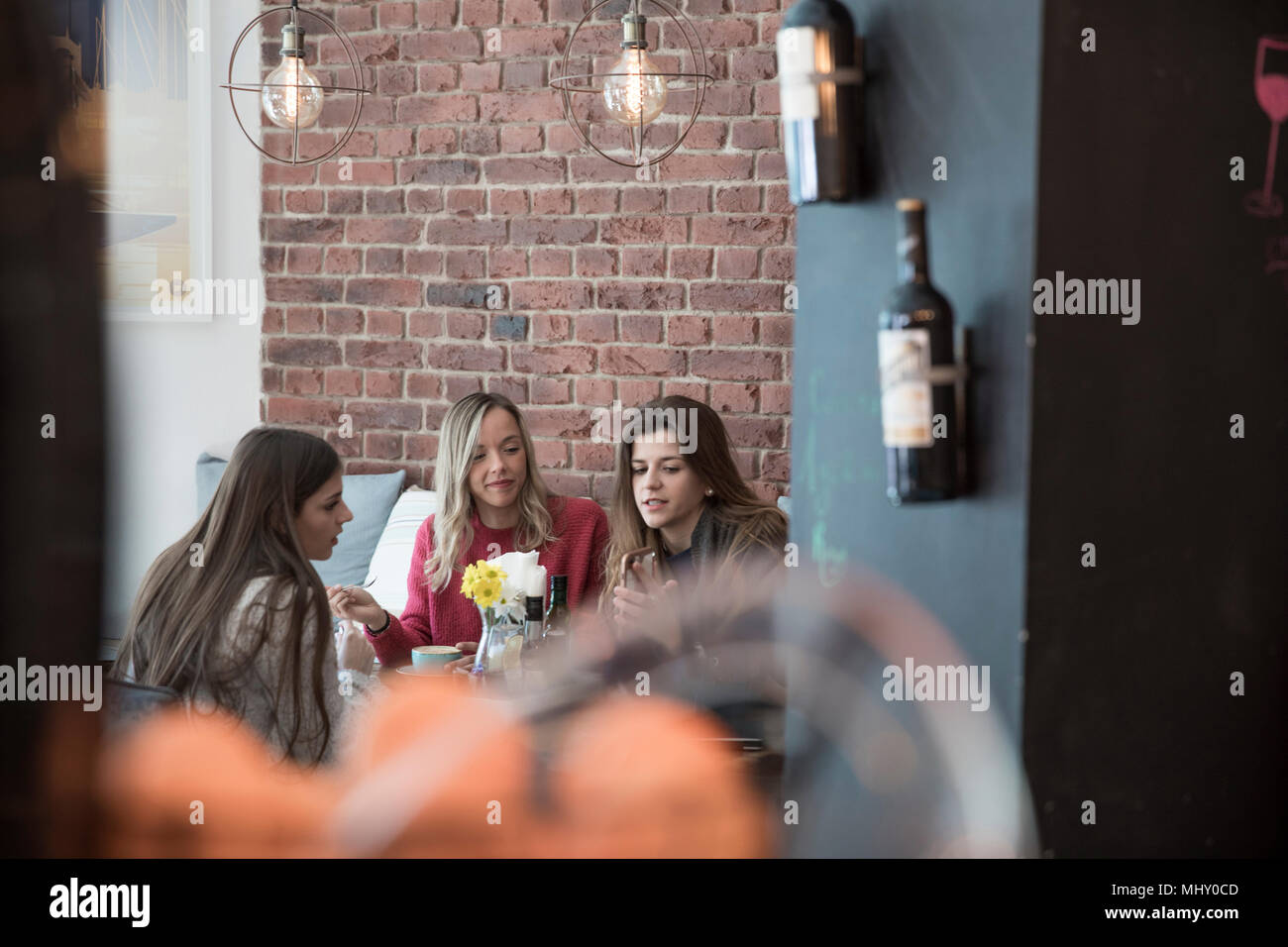 Female friends sitting together in cafe, looking at smartphone Stock Photo