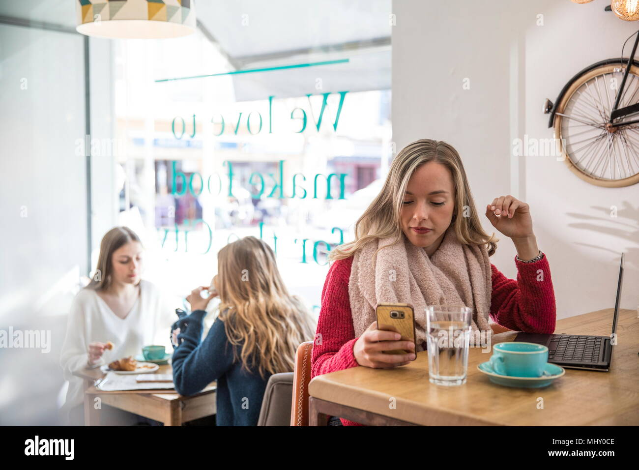 Woman sitting in cafe, looking at smartphone, laptop in front of her - Stock Image