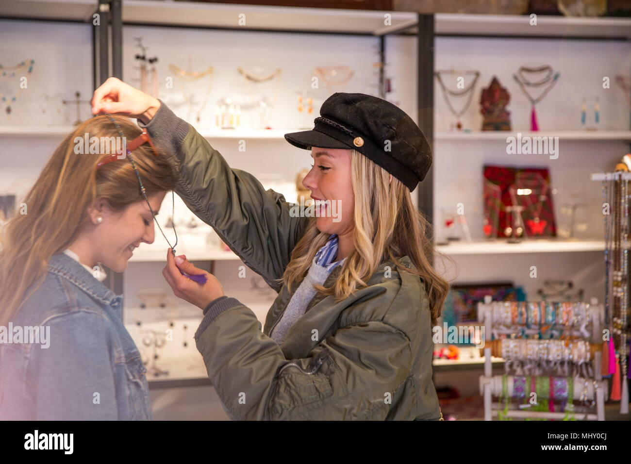 Two female friends, shopping, trying on necklace - Stock Image