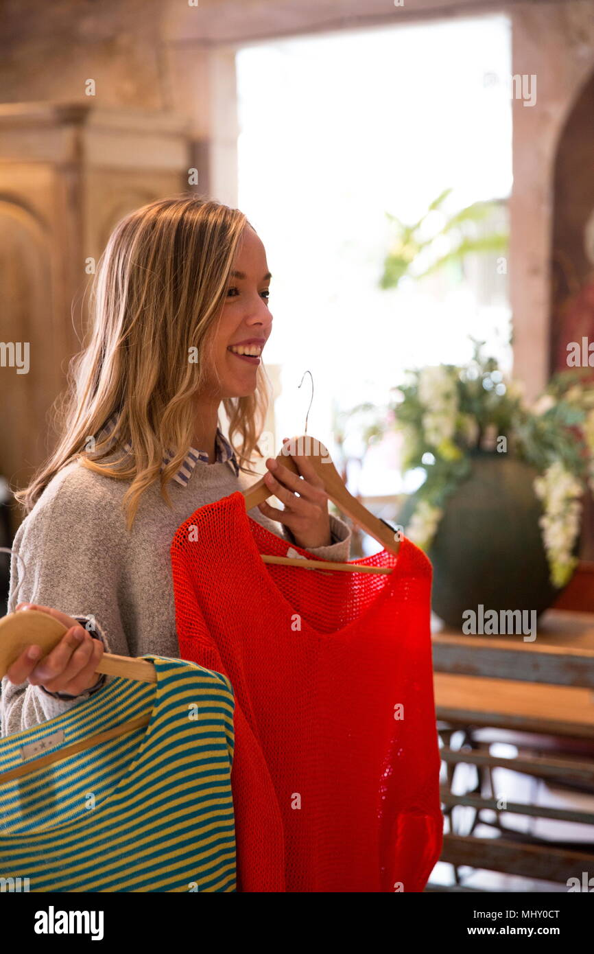 Young woman shopping, holding clothes up, making decisions - Stock Image