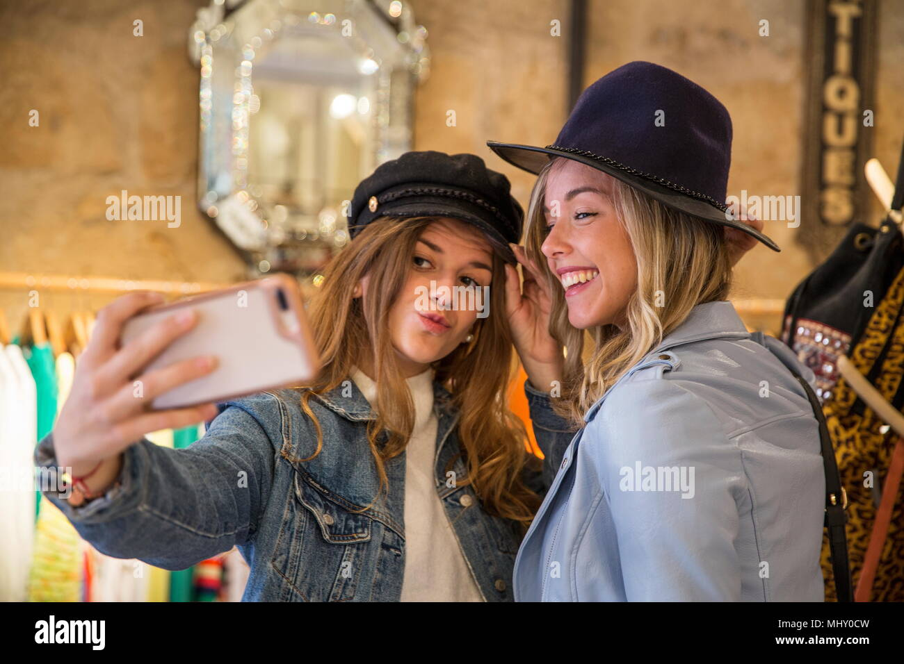 Two friends in shop, trying on hats, taking selfie, using smartphone - Stock Image
