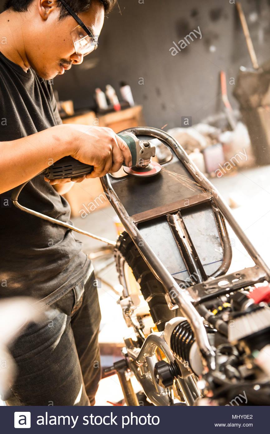 Mechanic working at custom motorbike shop, Bangkok, Thailand - Stock Image
