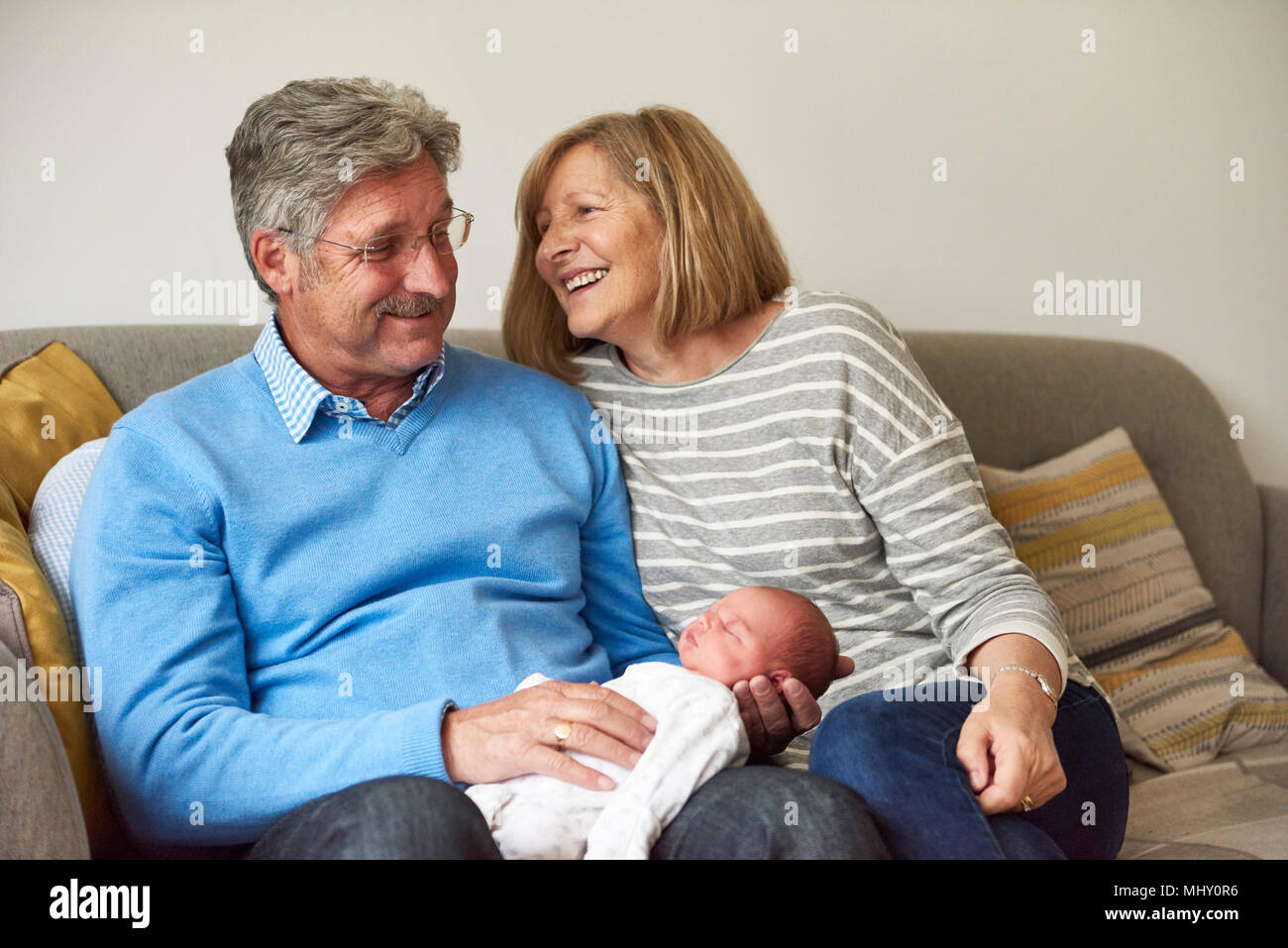 Grandparents on sofa with baby granddaughter - Stock Image