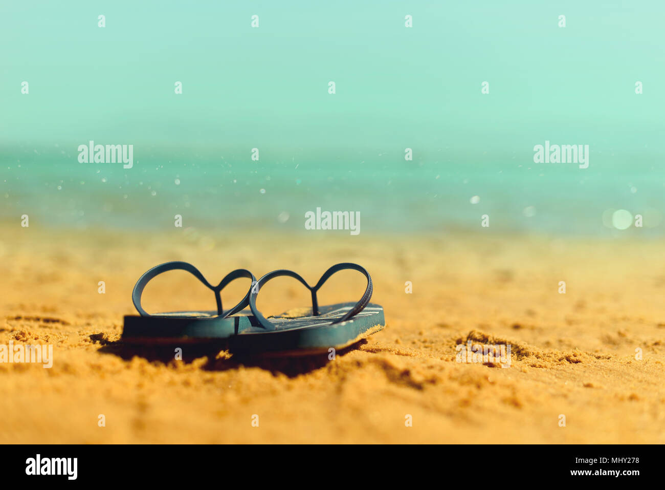 Navy flip flop on yellow sand beach with blue sea and sky background. Copy space. Summer, holiday and travel concept - Stock Image