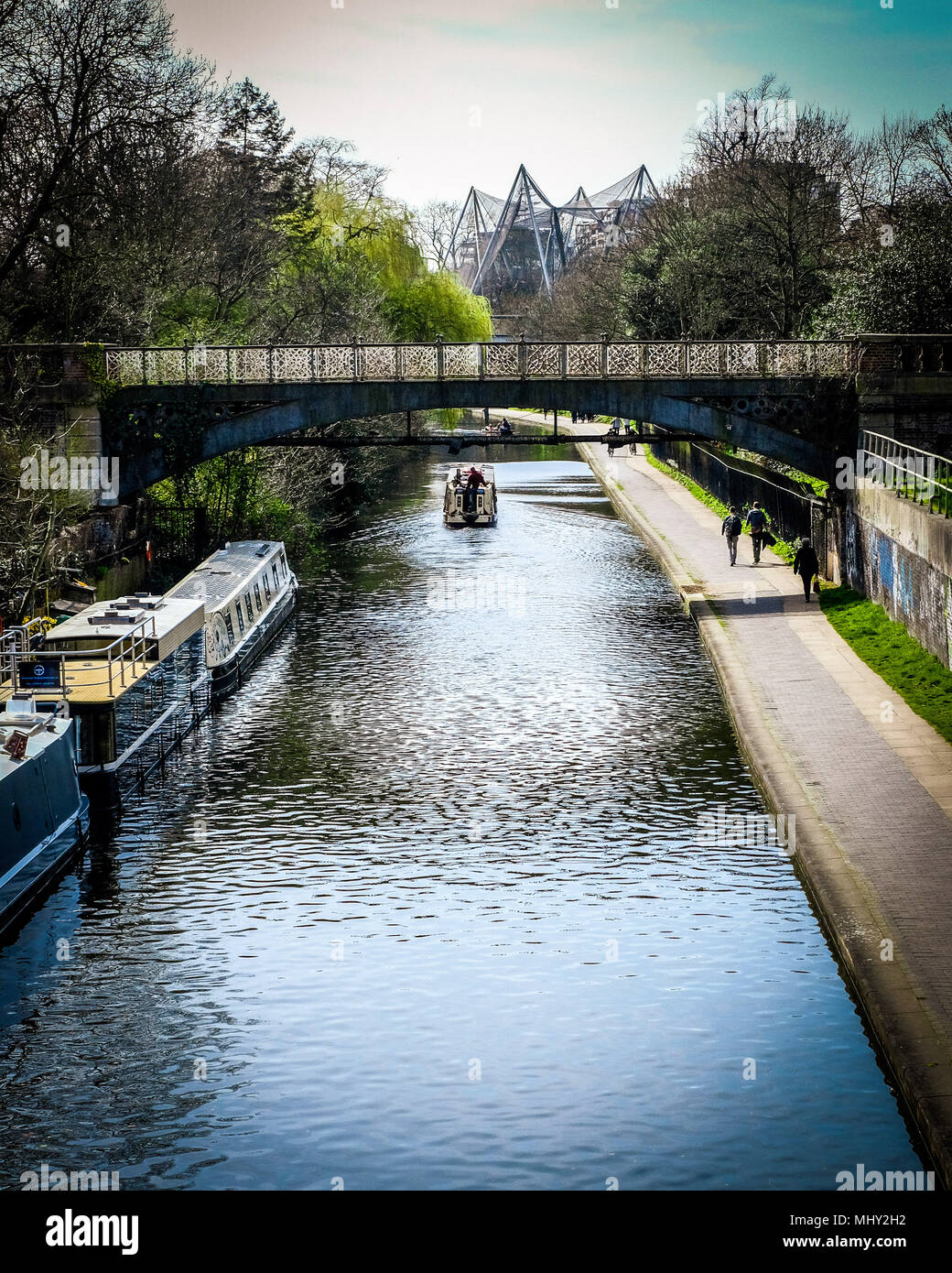 A narrow boat passes under a brigde on regents canal passing London Zoo in Regents Park, London Stock Photo