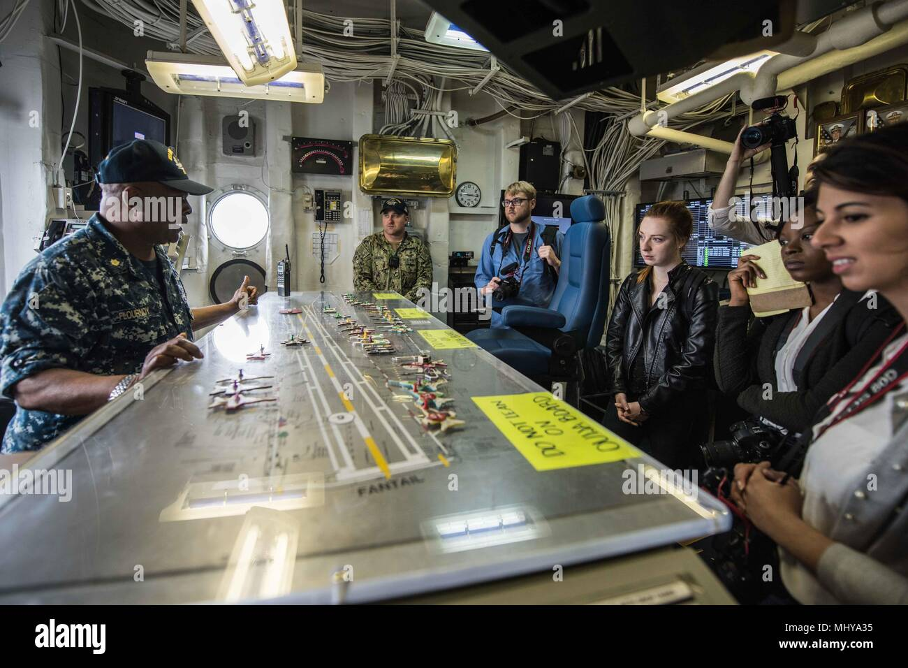 180503-N-CL027-0103 YOKOSUKA, Japan (May 3, 2018) Lt. Cmdr. Terrance Flournoy, the flight deck handler for the Navy's forward-deployed aircraft carrier, USS Ronald Reagan (CVN 76), explains flight deck operations to Northwestern University media students during a ship tour, May 3, 2018. During the tour, the students visited various locations throughout the ship including the flight deck, hangar bay and bridge. Ronald Reagan, the flagship of Carrier Strike Group 5, provides a combat-ready force that protects and defends the collective maritime interests of its allies and partners in the Indo-Pa - Stock Image