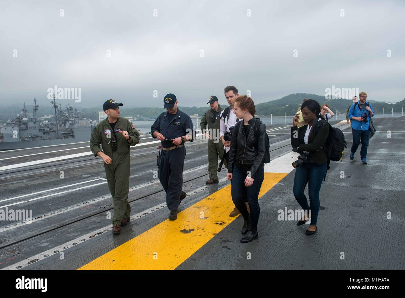 180503-N-CL027-0076 YOKOSUKA, Japan (May 3, 2018) Sailors aboard the Navy's forward-deployed aircraft carrier, USS Ronald Reagan (CVN 76), explains flight deck operations to Northwestern University media students during a ship tour, May 3, 2018. During the tour, the students visited various locations throughout the ship including the flight deck, hangar bay and bridge. Ronald Reagan, the flagship of Carrier Strike Group 5, provides a combat-ready force that protects and defends the collective maritime interests of its allies and partners in the Indo-Pacific region. (U.S. Navy photo by Mass Com - Stock Image
