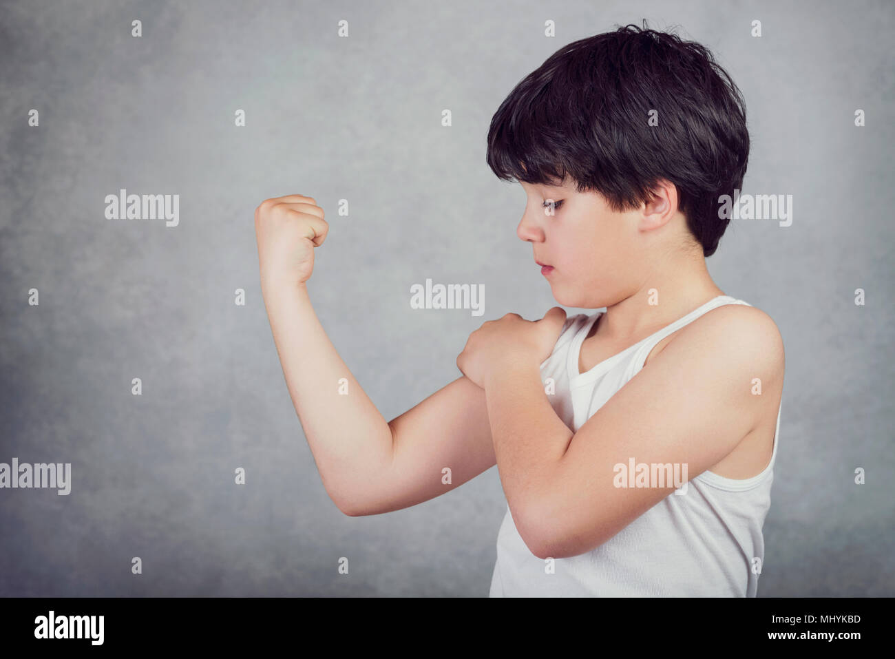 kid showing his muscles on gray background - Stock Image