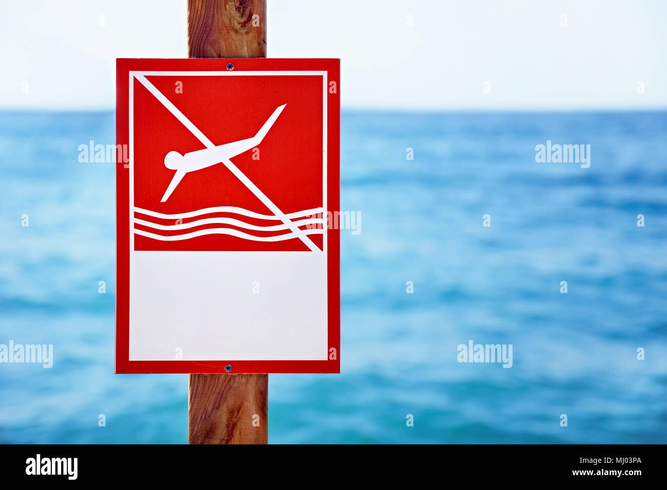 Red no diving sign nailed to a wooden plank in front of the blue sea background - Stock Image