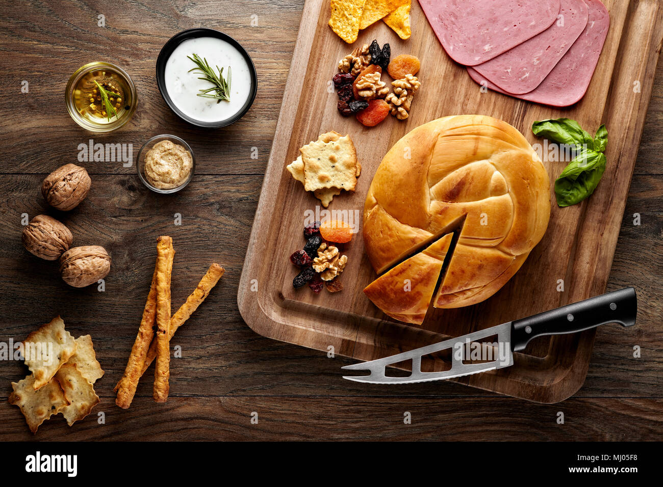 Turkish smoked cheese on a wooden table decorated with props of wooden cutting board, cheese knife, walnuts, dried fruits, ham and olive oil - Stock Image