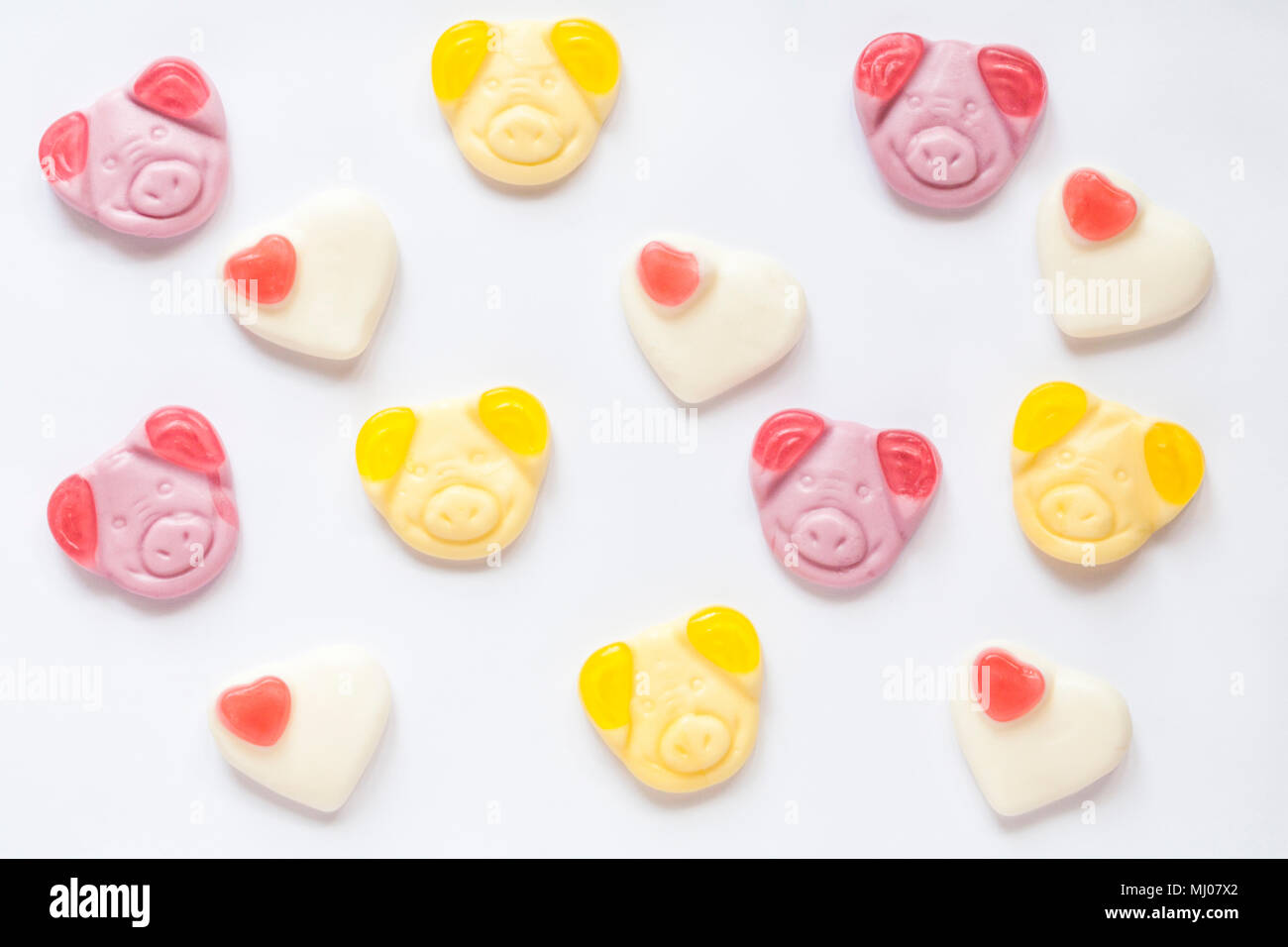 percy pig sweets congratulations percy and penny with strawberry hearts to celebrate the big day - set on white background - Stock Image