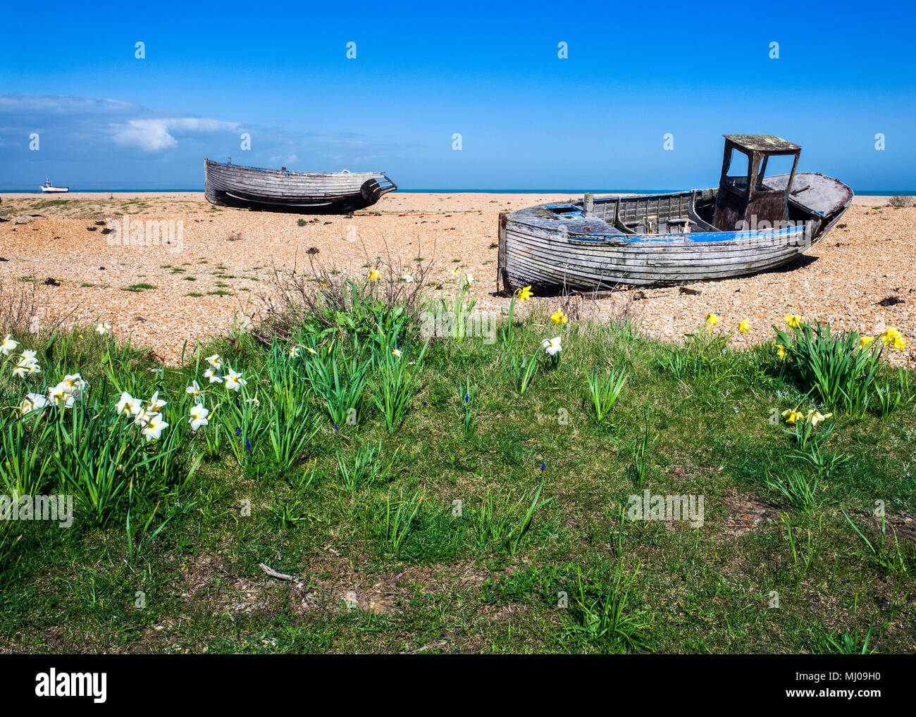 A derelict clinker-built wooden fishing boat with wheelhouse,abandoned on the shingle beach at Dungeness, Sussex, England Stock Photo
