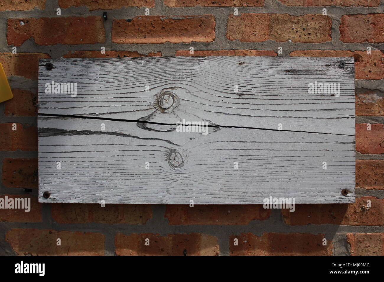 Weathered plank board screwed into a brick wall. - Stock Image