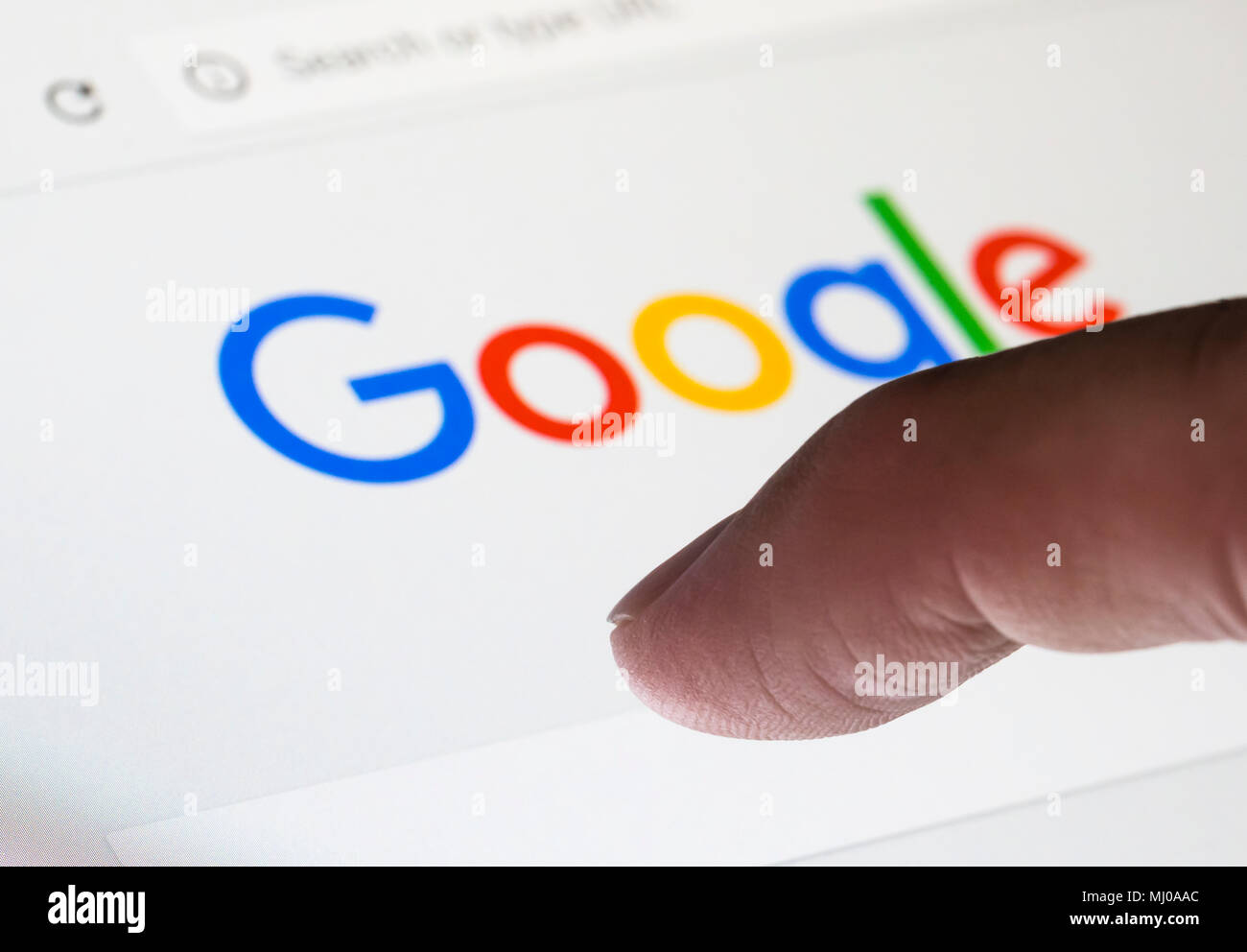 Finger about to type a search on the Google Internet search engine website. - Stock Image