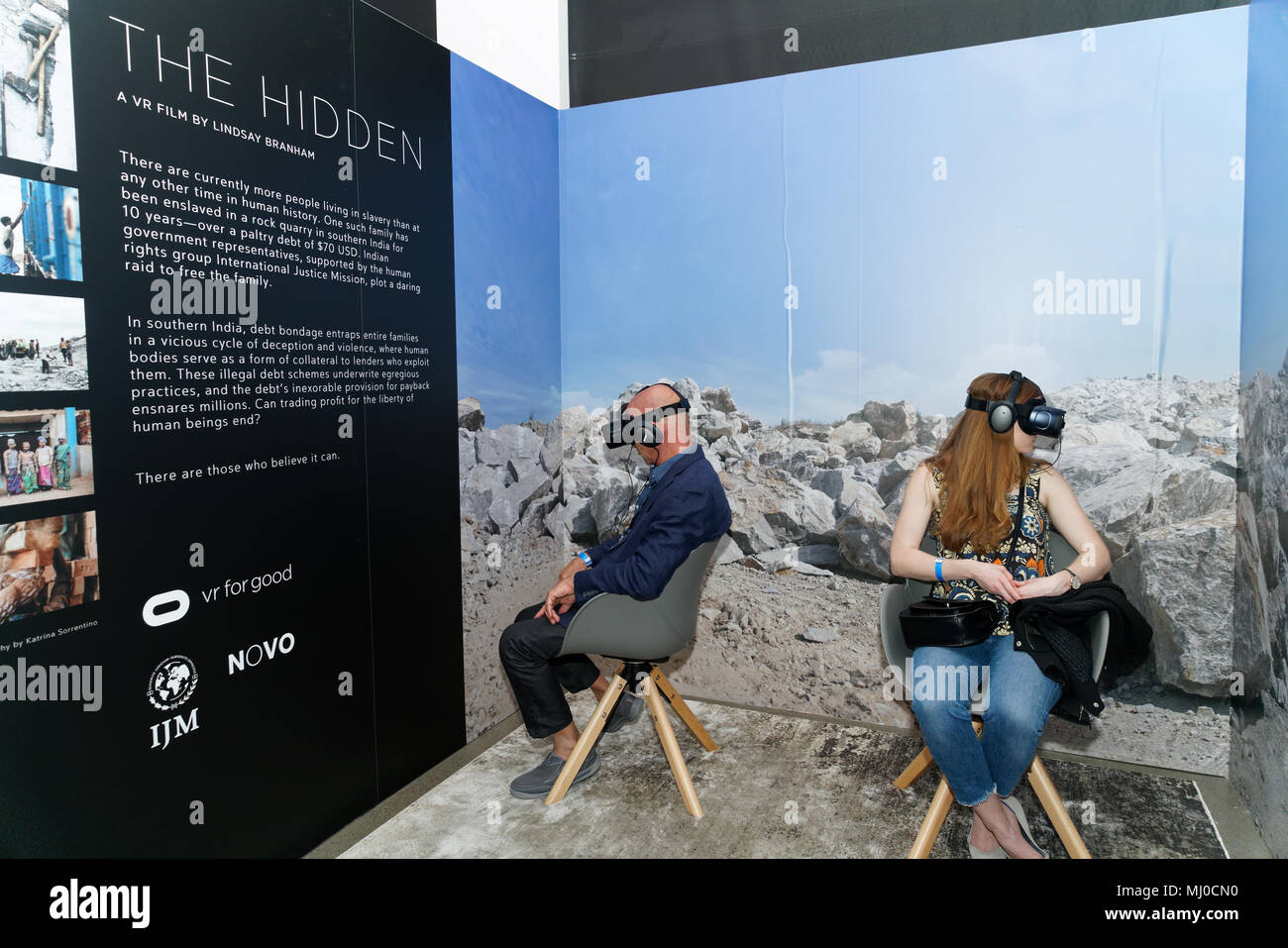 "Visitors to the Tribeca Film Festival Virtual Arcade watching ""The Hidden,"" which tells the story of a family enslaved for 10 years in India. - Stock Image"