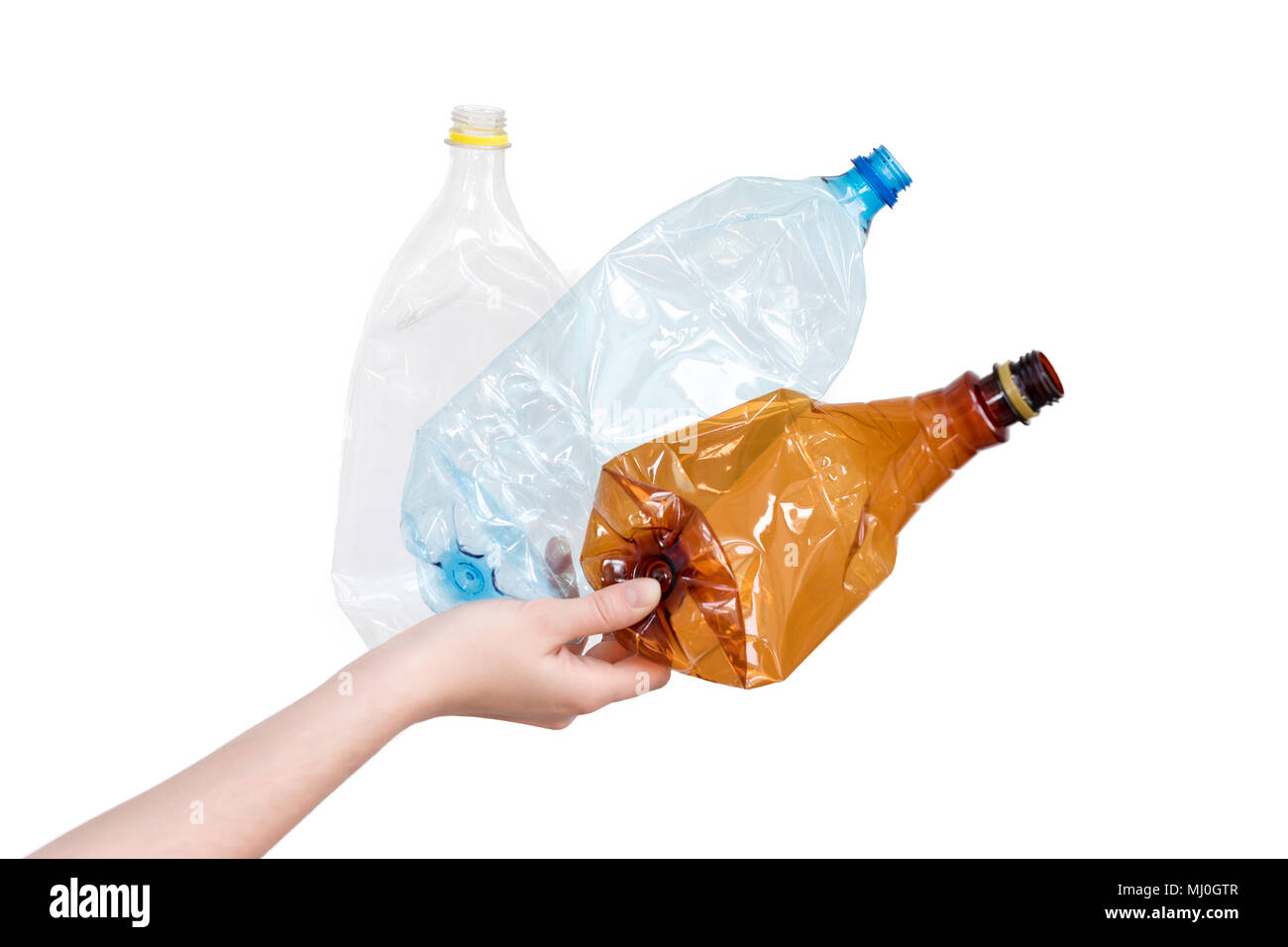 Female hand holding different types of crushed plastic bottles isolated on white. Recyclable waste. Recycling, reuse, garbage disposal, resources, environment and ecology concept - Stock Image
