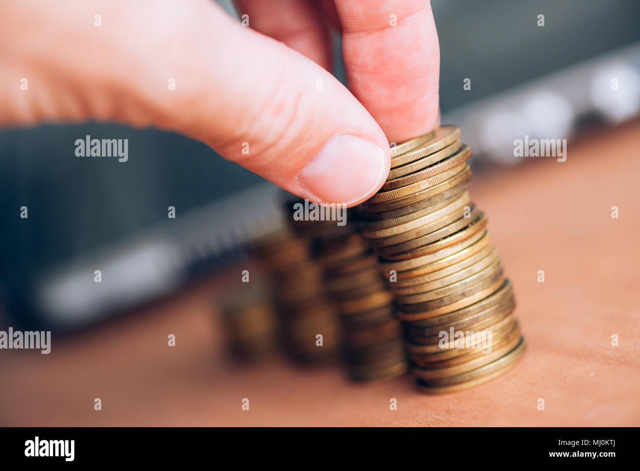Close up of male hand stacking coins. Money savings and budgeting concept. - Stock Image