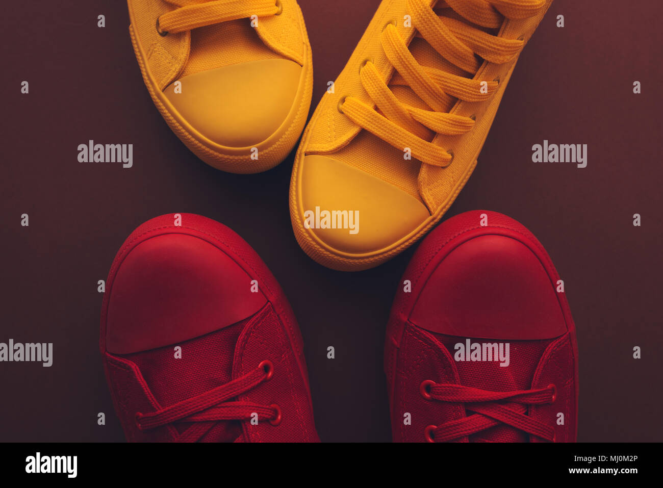 Young people on a love date, conceptual image. Top view of two pair of casual sneakers, yellow and red, from above close to and facing each other like Stock Photo
