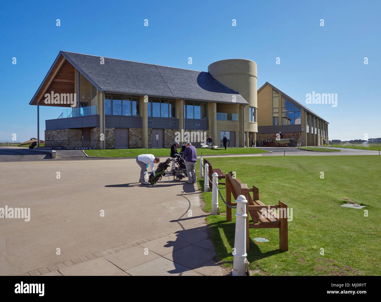 Golfers getting ready to play in front of the New Carnoustie Golf centre and Clubhouse, at the Open Championship Course at Carnoustie Links, Angus. - Stock Image