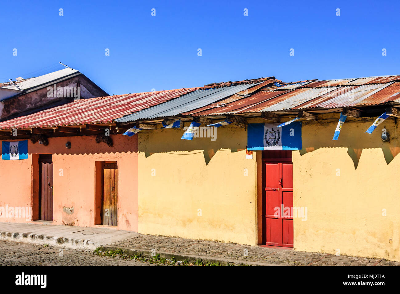 Antigua, Guatemala - October 5, 2014: Old, colorful, painted houses adorned with Guatemalan flags in UNESCO World Heritage Site of Antigua - Stock Image