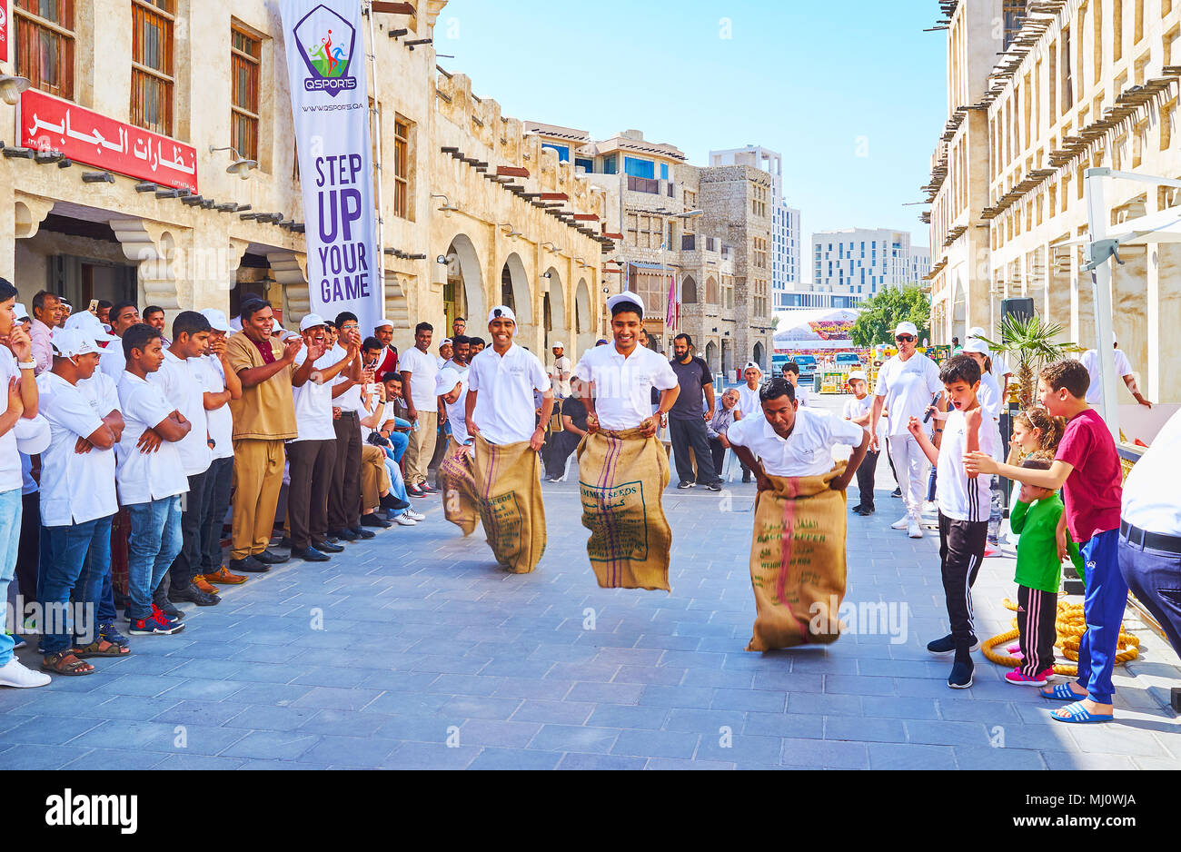 DOHA, QATAR - FEBRUARY 13, 2018: The  sack race in street of Souq Waqif - people celebrate the Day of Sport, playing fun active games, on February 13  - Stock Image
