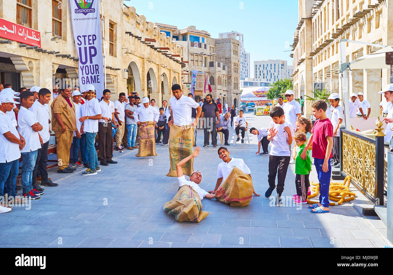 DOHA, QATAR - FEBRUARY 13, 2018: The celebration of Day of Sport - the sack race among the young workers of cafes and restaurants in Souq Waqif, on Fe Stock Photo