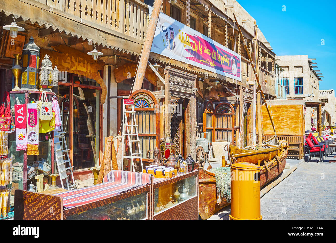 DOHA, QATAR - FEBRUARY 13, 2018: The facade of antique store in Souq Waqif is decorated with outstanding woodwork, old carved wares, dhow boat and Ara - Stock Image