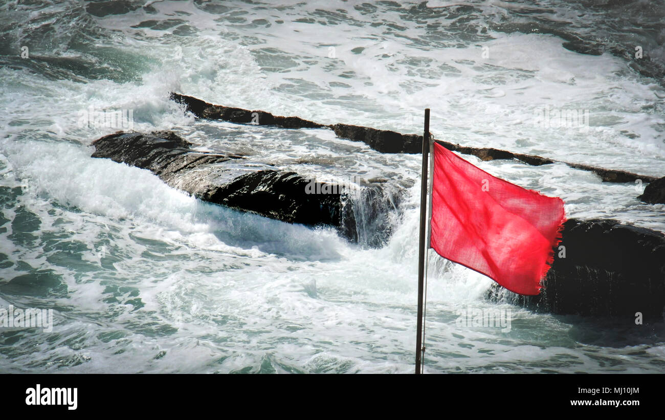 red flag sea rocks rough storm gale wind alert background - Stock Image