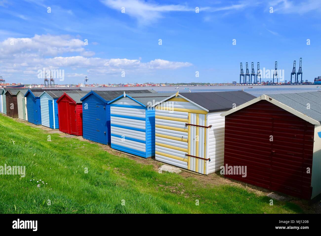 Colourful beach huts on the harbour wall at Harwich, Essex. Bright sunny day. May 2018. Port of Felixstowe cranes visible in the background. - Stock Image