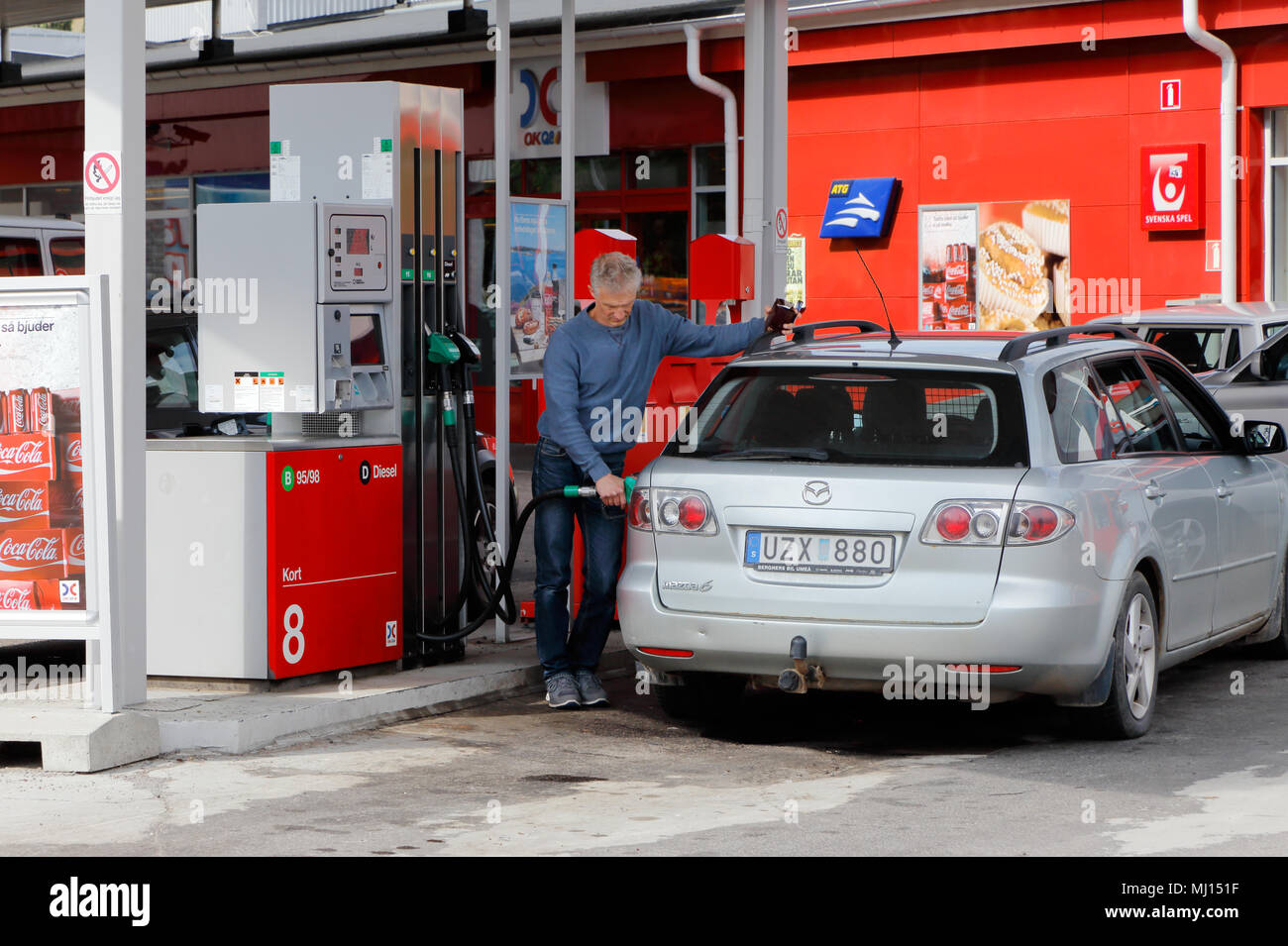 Ornskoldsvik, Sweden - July 14, 2015: One person refueling a car at a self service gas station in service fpr the brand OKQ8. - Stock Image