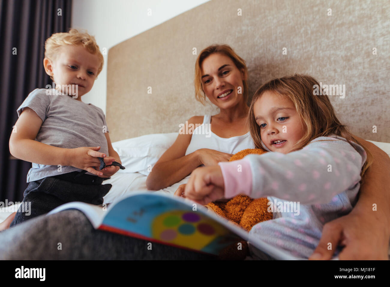 Young mom with her children on bed reading a story book. Cute little girl pointing at storybook while sitting with her mother and brother on bed. Stock Photo